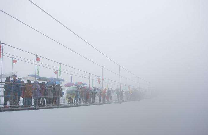 توریست ها در چین استان هونان در حال عبور از پل معلق کف شیشه ای