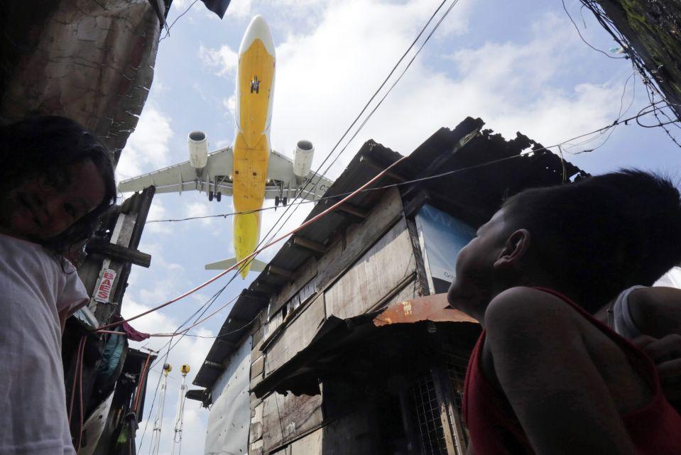 عبور هواپیمای مسافربری با ارتفاع پایین از فراز منطقه ای حومه ای در جنوب شهر مانیل فیلیپین